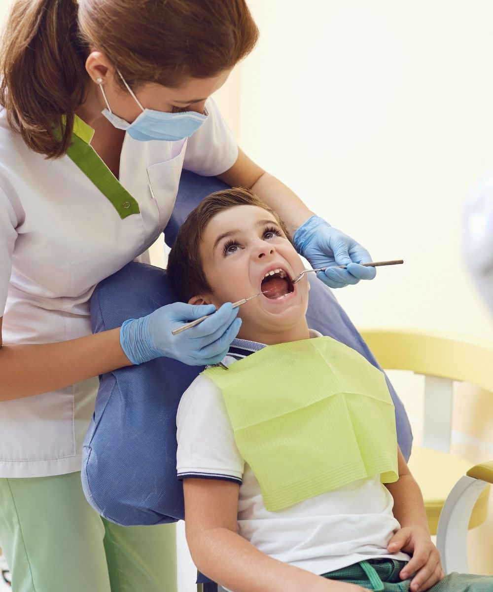 Kid at the dentist getting check by a female dentist