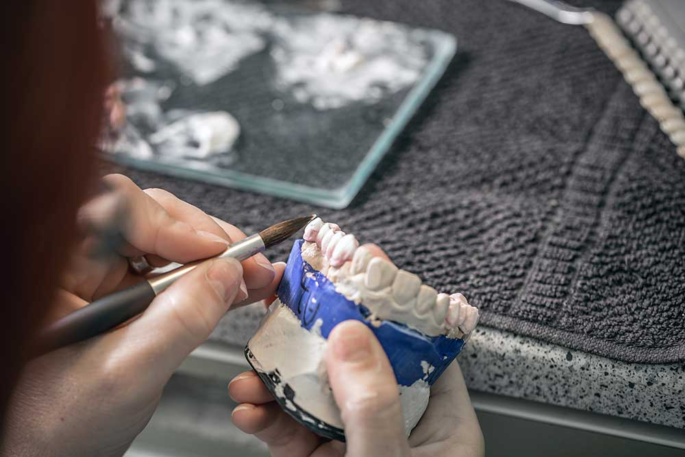 woman hand painting dentures