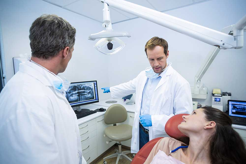dentist showing xray of teeth to female